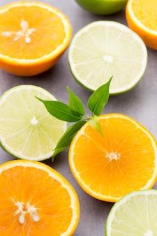 Gemengde citrusvruchten citroenen, sinaasappel, kiwi, limoenen (lemmetjes) op een grijze achtergrond.