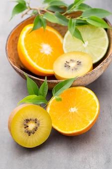 Gemengde citrusvruchten citroenen, sinaasappel, kiwi, limoenen op een grijs