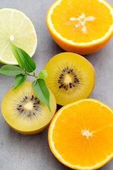 Gemengde citrusvruchten citroenen, sinaasappel, kiwi, limoenen op een grijze ondergrond.