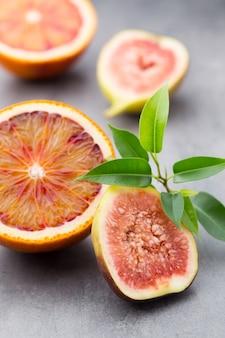 Gemengde citrusvruchten sinaasappel, vijgen, limoenen op een grijze ondergrond.