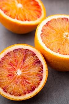 Gemengde citrusvruchtensinaasappel, vijgen, limoenen op een grijze achtergrond.