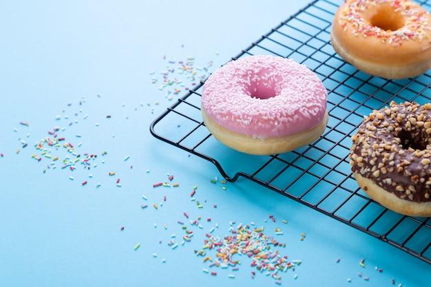 Gemengde donuts op net op blauwe achtergrond. met kopie ruimte.
