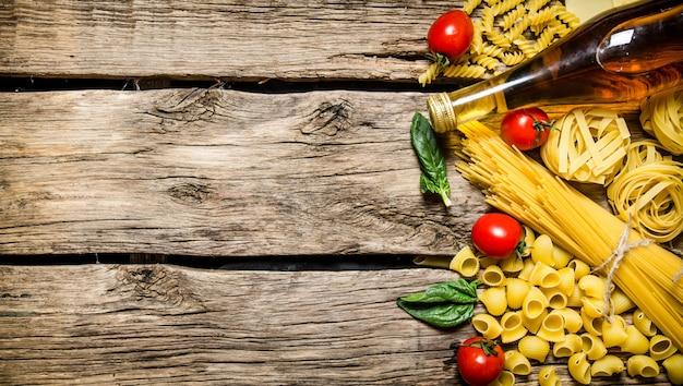 Gemengde droge pasta en spaghetti, met tomaten, kruiden en olijfolie. op houten achtergrond. vrije ruimte voor tekst. bovenaanzicht