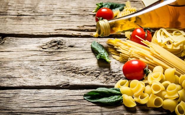 Gemengde droge pasta en spaghetti, met tomaten, kruiden en olijfolie. op houten achtergrond. vrije ruimte voor tekst.