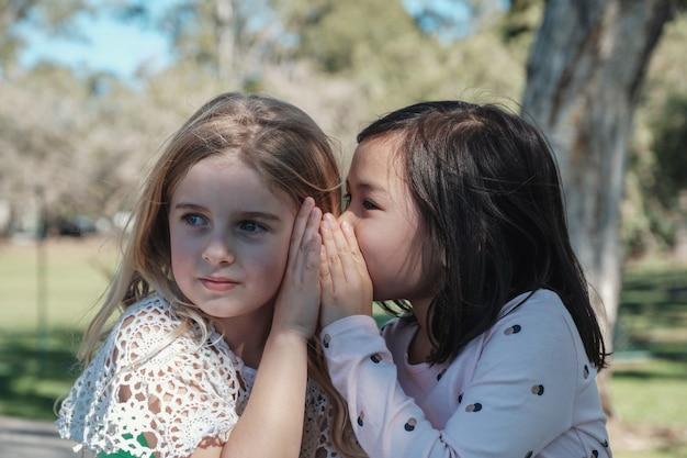 Gemengde etnische jonge meisjes die chinees spelen die in het park fluisteren