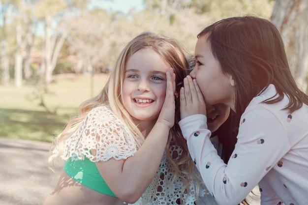 Gemengde etnische jonge meisjes die jonge geitjes chinees spelen die in het park, beste vrienden en positieve vriendschap, het concept van beste vrienden voor altijd fluisteren