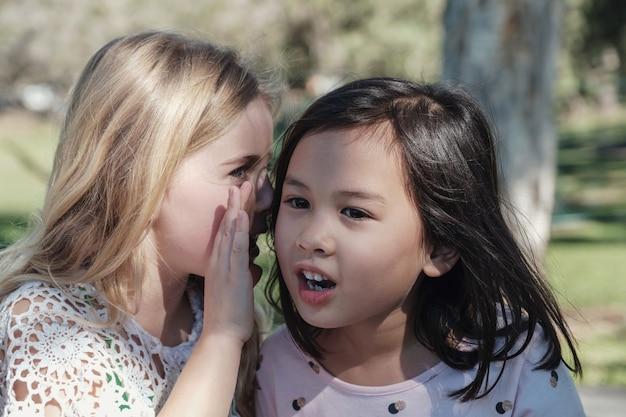 Gemengde etnische jonge meisjes die jonge geitjes chinees spelen die in het park fluisteren