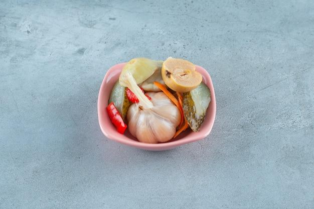 Gemengde gefermenteerde groenten in een plastic kom op het blauwe oppervlak