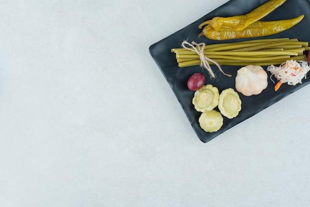 Gemengde gefermenteerde groenten op zwarte plaat.