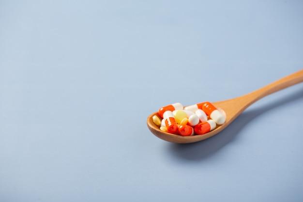 Gemengde geneeskundepillen, tabletten op houten lepel