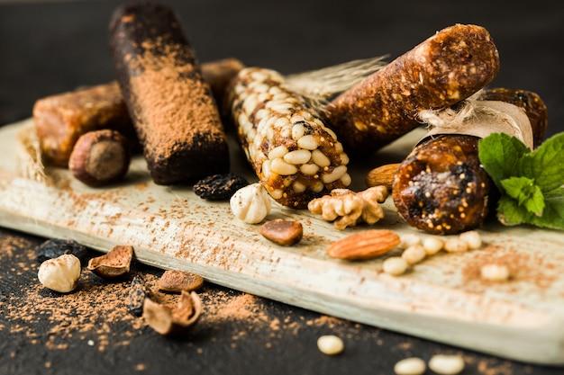 Gemengde glutenvrije granola energierepen met gedroogd fruit & diverse noten, houten wand. gezond veganistisch superfood, verschillende fitnessdieetsnacks voor een sportieve levensstijl.