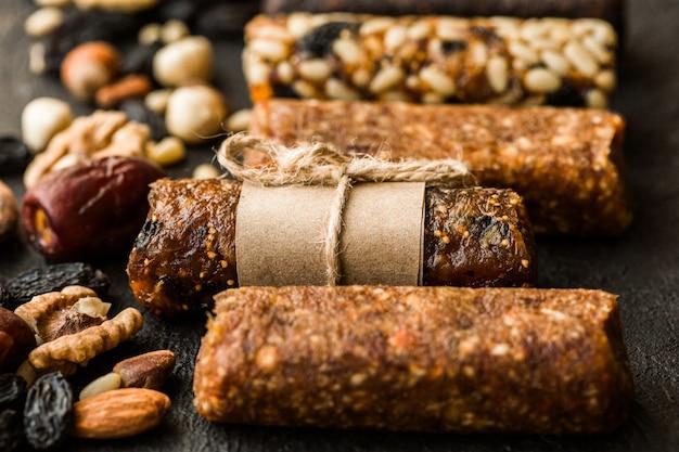 Gemengde glutenvrije granola-energierepen met gedroogd fruit en verschillende noten op een betonnen muur. gezond veganistisch superfood, verschillende fitnessdieetsnacks voor een sportieve levensstijl.