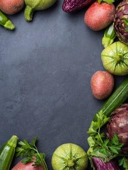 Gemengde groene en paarse groenten op zwart