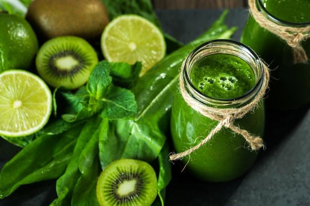 Gemengde groene smoothie met ingrediënten op het stenen bord, houten tafel