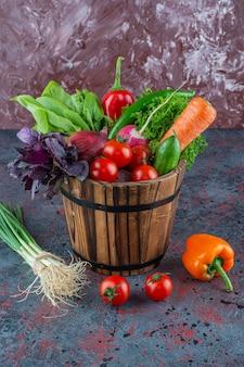 Gemengde groenten in een emmer op het marmeren oppervlak