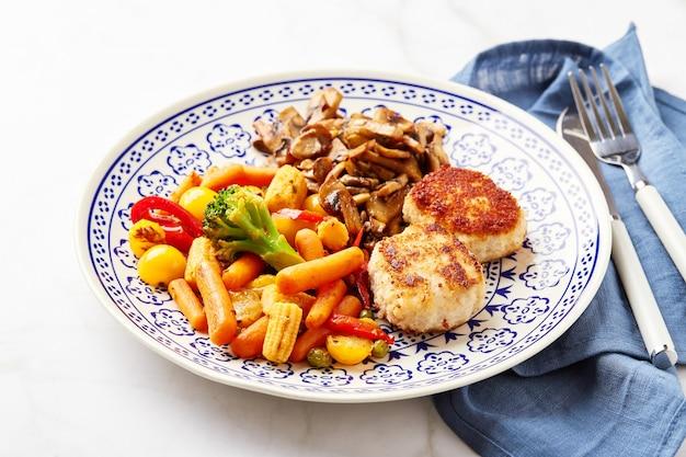 Gemengde groenten van wortelen, broccoli, babymais, paprika, geroosterde champignons en twee kippasteitjes in paneermeel
