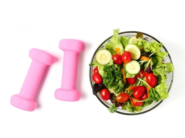 Gemengde groentesalade en geschiktheidsapparatuur op witte achtergrond.