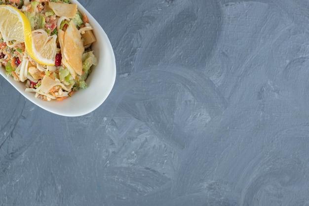 Gemengde groentesalade gegarneerd met plakjes citroen op marmeren tafel.