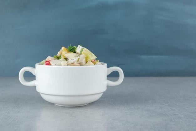Gemengde ingrediëntengroente en fruitsalade in een witte kop.