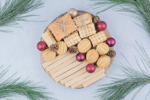 Gemengde koekjes en kerst ornamenten op een houten bord.