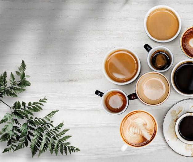 Gemengde koffiekopjes met een blad op een wit houten structuurbehang