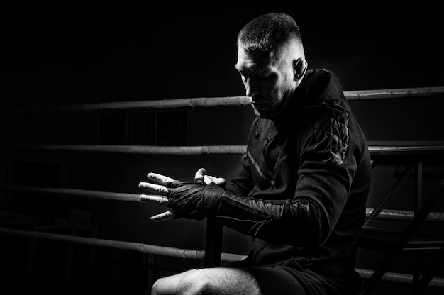 Gemengde krijgskunstenaar wikkelt verband om zijn vuist. concept van mma, ufc, thai boksen, klassiek boksen. gemengde media