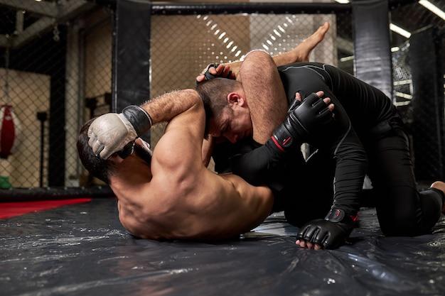 Gemengde krijgskunstenaars die elkaar slaan, vechten zonder regels in de sportschool, trainen. agressieve boksers die sparren, sterke krachtige spieren hebben, op de begane grond liggen