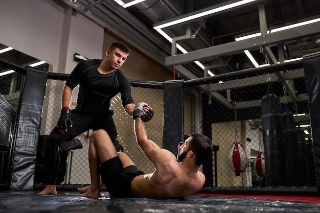 Gemengde krijgskunstenaars tijdens gevecht, help elkaar, in ring op sportschool. man in zwarte kleding steekt hand uit naar man zonder shirt, bezig met kickboksen