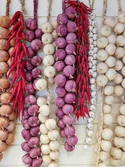 Gemengde kruiden spaanse pepers, uien en garlics hangen op witte houten achtergrond. voedsel