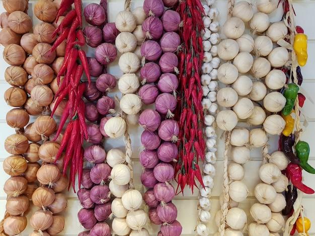 Gemengde kruiden spaanse pepers, uien en garlics hangen op witte houten achtergrond