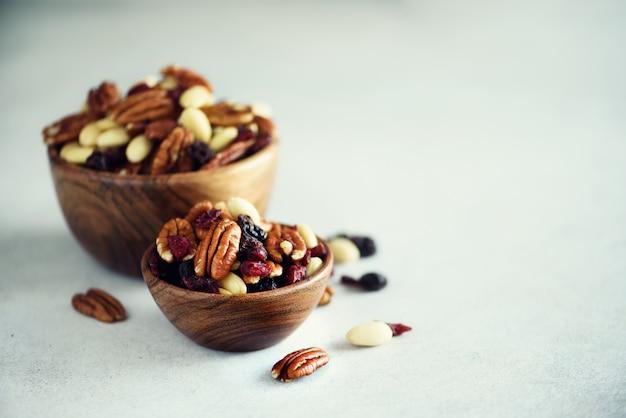 Gemengde noten en rozijnen in houten kom.