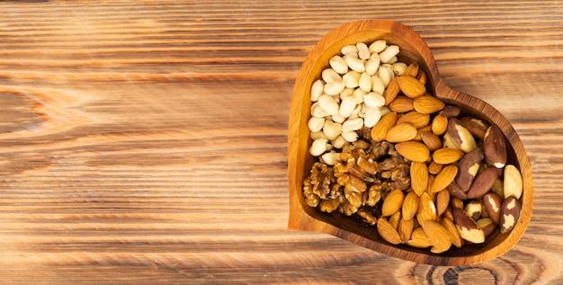 Gemengde noten in een kom in de vorm van een hart op een bruine houten ondergrond