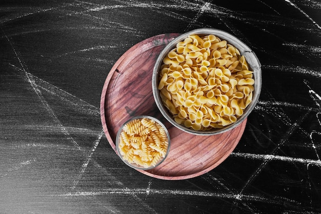 Gemengde pasta's in metalen kopjes op een houten schotel.