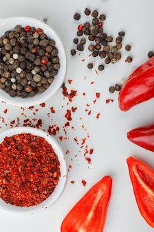 Gemengde peper in een plaat met chilipoeder en rode pepers close-up op een witte muur