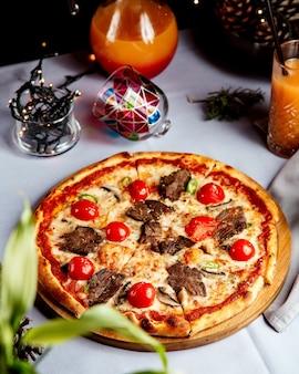 Gemengde pizza met stukjes vlees en tomaat