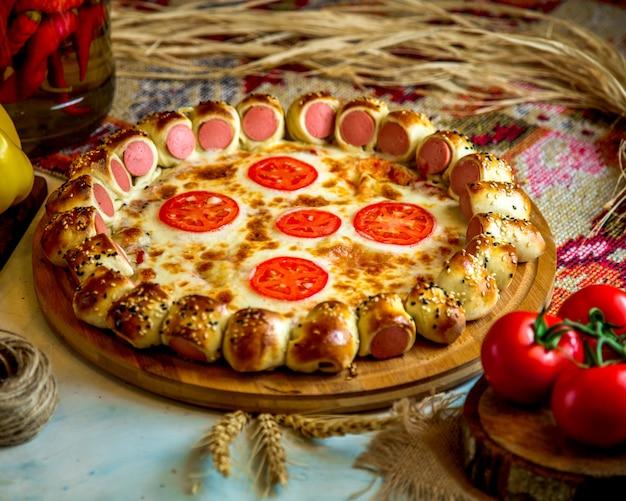 Gemengde pizza met worstjes en tomaat