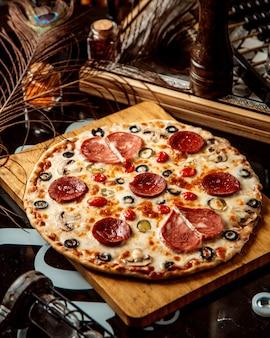 Gemengde pizza met worstjes olijven en tomaat