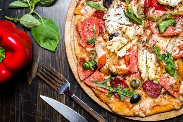 Gemengde pizza worstjes kip arugula olijven kaas peper bovenaanzicht