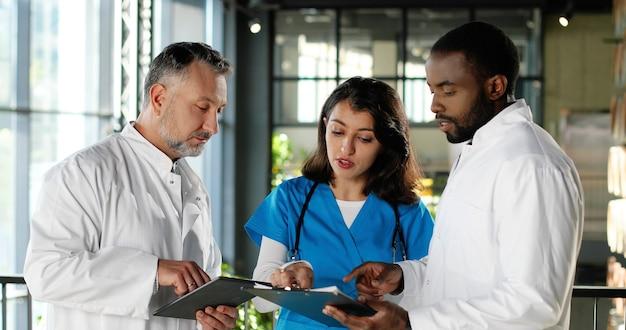 Gemengde rassen mannetjes en vrouwelijke artsen praten in de kliniek. multi-etnische mannen en vrouwen, medici met discussie in het ziekenhuis. arts met verpleegster die ziekte bespreekt. documenten en assistent. gesprek.