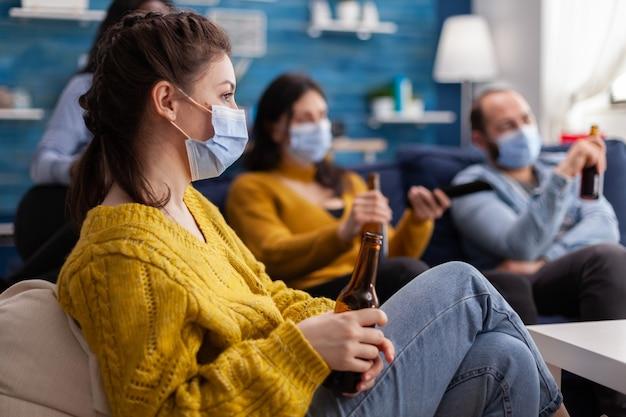 Gemengde rassen van vrienden die naar tv kijken, man met afstandsbediening die gezichtsmasker draagt vanwege de uitbraak van een pandemie van het coronavirus bier drinken, ontspannen, zittend op de bank in de woonkamer.