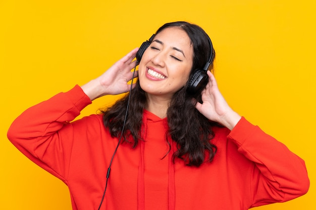 Gemengde rasvrouw die een rode sweater het luisteren muziek draagt