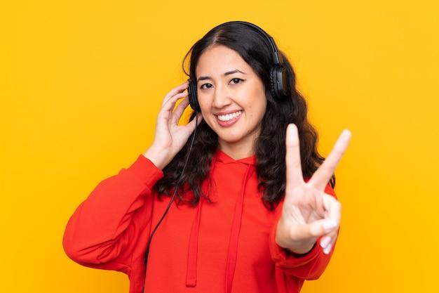 Gemengde rasvrouw die een rood sweatshirt het luisteren muziek en het zingen draagt