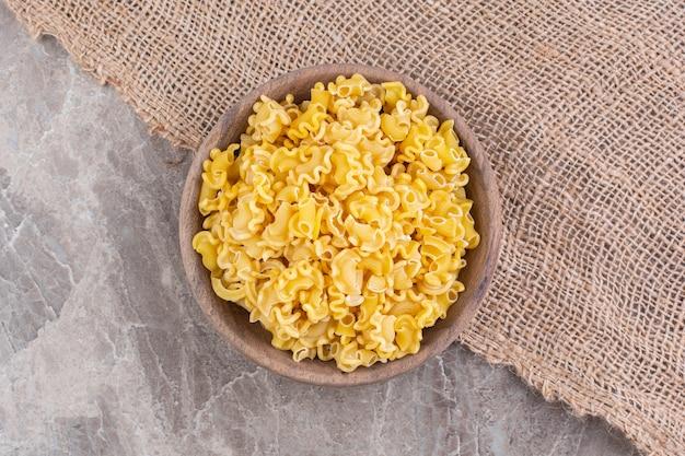 Gemengde rauwe pasta in een kom op een jute, op het marmeren oppervlak