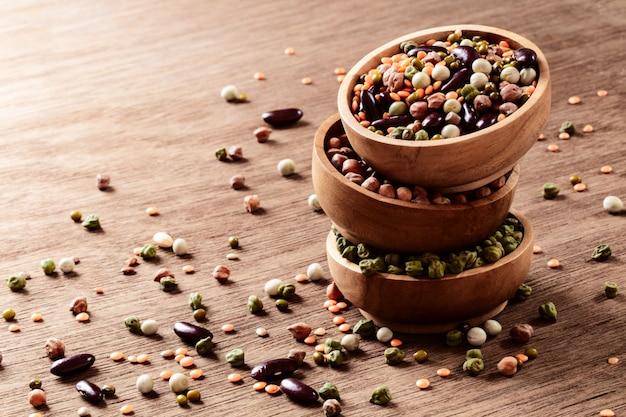 Gemengde ruwe droge indische peulvruchten in houten kommen op rustieke achtergrond met copyspace.