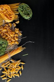 Gemengde ruwe pasta op zwarte achtergrond