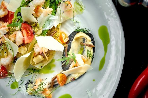 Gemengde salade met gegrilde garnalen, parmezaan en artisjok geserveerd in een wit bord op een donkere marmeren tafel. restaurant eten.