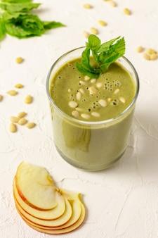 Gemengde smoothie van groen fruit in glas met pijnboompitten