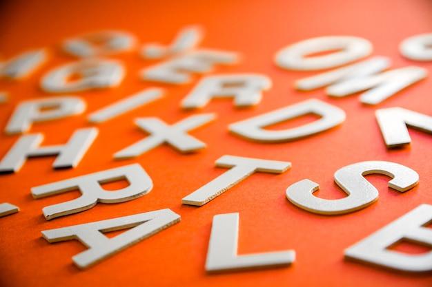 Gemengde stevige letters stapelen close-up foto bekijken. onderwijsconcept op oranje achtergrond.