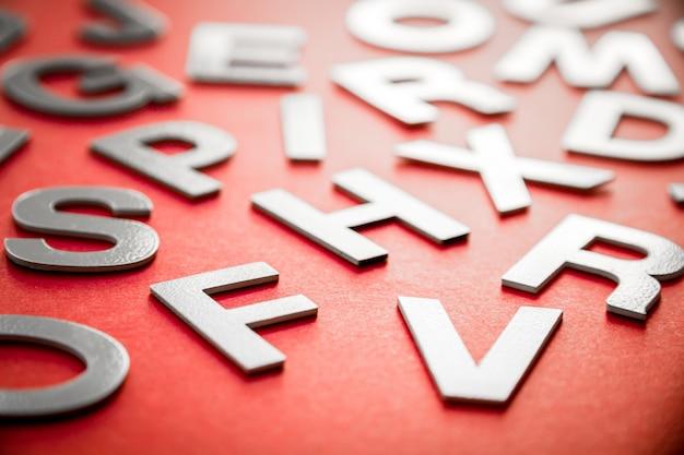 Gemengde stevige letters stapelen close-up foto bekijken. onderwijsconcept op rode achtergrond.