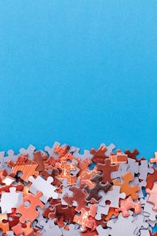 Gemengde stukken van een kleurrijke legpuzzel liggen op de blauwe achtergrond met kopieerruimtestrategie en zo...